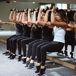Several women in workout clothes performing the chair exercise against a mirror while holding weights }
