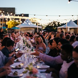 People sitting around a long table outside with food and drinks and festoon lighting}