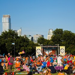 A crowd on the green on a sunny day with a stage in the background and the Austin skyline beyond}