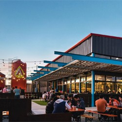 Exterior of Austin Beerworks, with festoon lighting above outdoor seating}