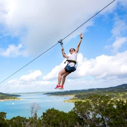 Woman ziplining over Lake Travis}