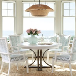 A white and metal dining room table and chairs in front of a bay window overlooking water}