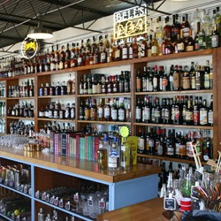 Shelves lined with bottles of spirits, beers and wines}