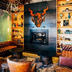 Leather seating around a fireplace with the gargoyle logo of Stone Brewing.}