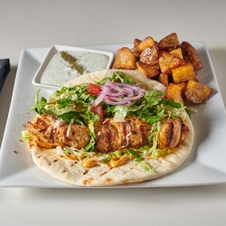 Chicken kabab on pita and potatoes on a square white plate}