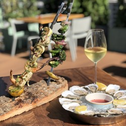 A wood table with skewers of shrimp and veggies, plus a plate of iced oysters, on a sunny patio}
