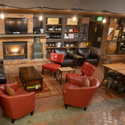 Several seating areas and a fireplace in the Woodinville tasting room of Alexandria Nicole Cellars.}
