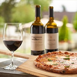 Two bottles of wine and a glass of red, plus a pizza in an outdoor setting.}