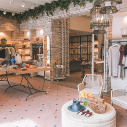Inside State & First, a boutique with curated items on tables, shelves and hangers