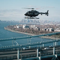 Bell Helicopter flying over a bridge with New York City skyline and river in the background