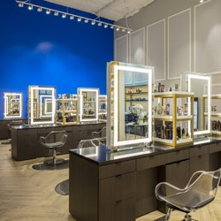 Salon stations with lighted mirrors and a blue wall in the background