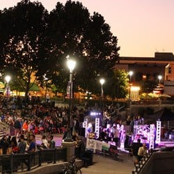 A large crowd of people listening to a band play outside on a warm evening in Napa