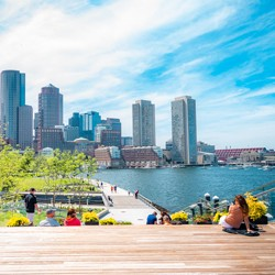 Daytime view of Boston Harbor with people walking along the shorline walkway and buildings in the background.
