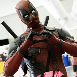 Deadpool cosplay giving the 'heart' handsign to the camera