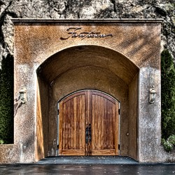 Exterior entry of Fantesca built into the side of the hill, with 2 curved wooden doors