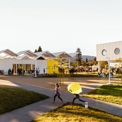 Exterior photo of two children running on a path in front of two mid-century modern buildings and an outside seating area.