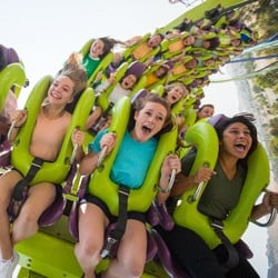 Closeup of people riding an upside-down roller coaster