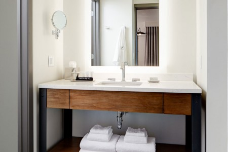 Luxe bathroom with vanity, mirror and Malin+Goetz bath amenities