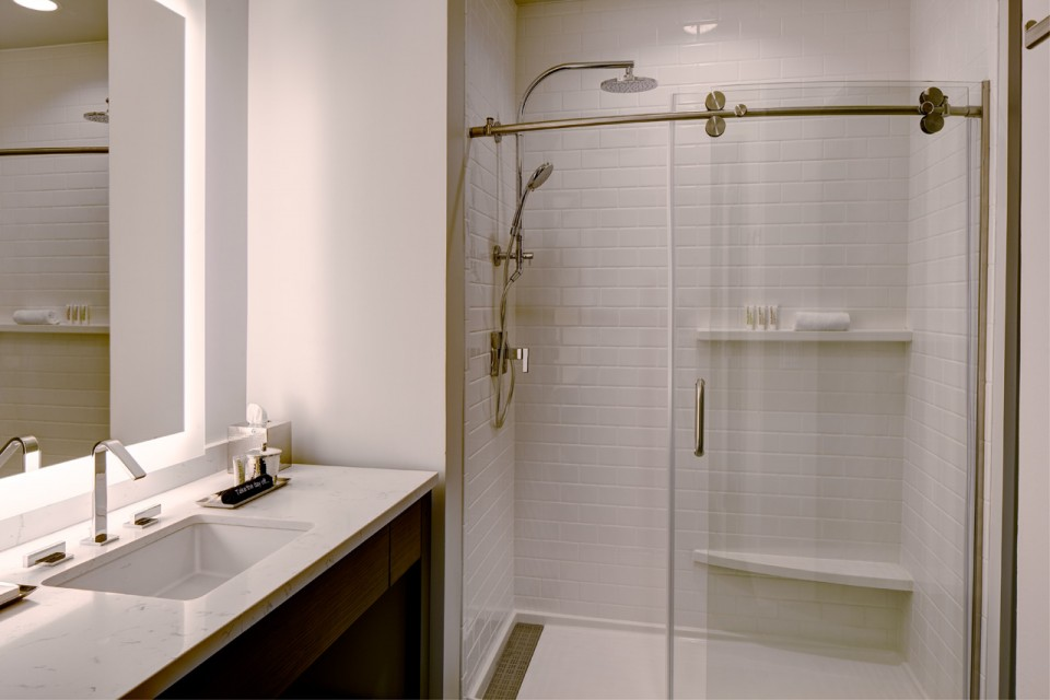 Modern bathroom with vanity and white subway-tile walk-in shower