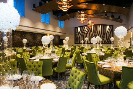 Venue with set tables, green chairs and white balloons