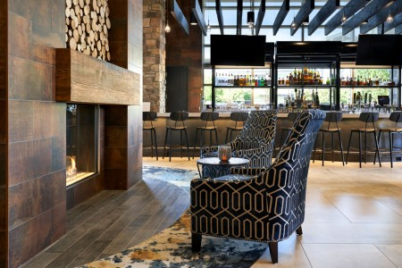 Fireplace with seating and Archer's Kitchen + Bar in background