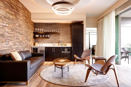 Archer's Den - separate living area with leather sofa, two chairs and a wet bar