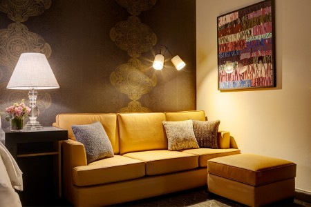 Deluxe King - ochre leather sofa with ottoman and wine-inspired artwork