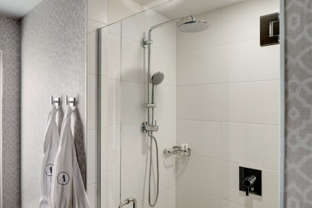 White porcelain tiled walk-in shower with two Frette robes hanging nearby