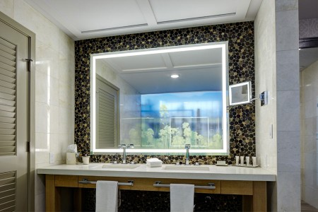 Archer's Den - white marble double vanity accented with a lit mirror against glass mosaic