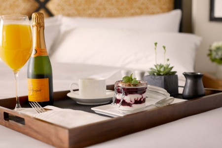 In-room dining featuring a breakfast tray and mimosa