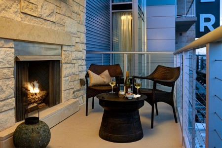 Balcony experience with lounge seating and limestone fireplace
