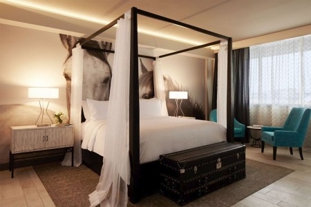 Archer King Suite - four-poster bed, two lounge chairs and horse mural