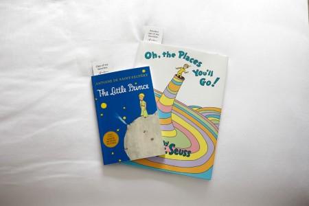 Two Massachusetts-inspired books on white bedding