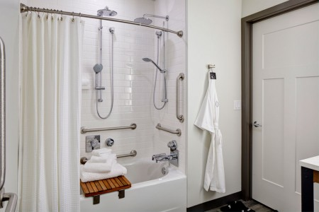Mobility-accessible bathroom featuring a roll-in shower with shower seat, hand-held shower wand and grab bars