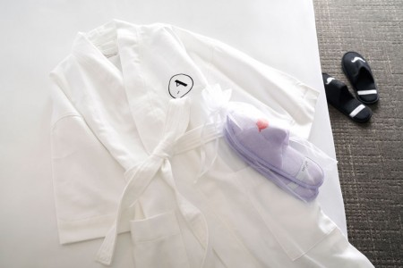 Frette bathrobe on bed with whimsical slippers