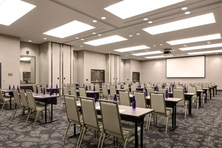 Great Room — Conference setup with tables and chairs, plus projector screen