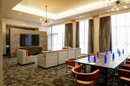 Hospitality Lounge — table with water bottles and chairs, plus soft seating and a flat-screen TV