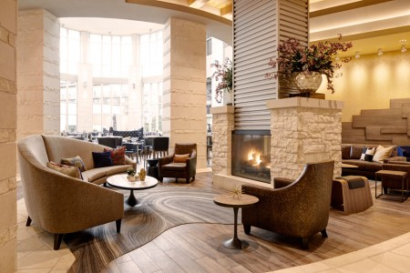 Lobby limestone fireplace with seating and Second Bar + Kitchen in the background