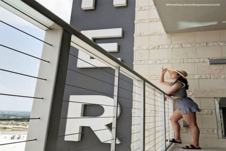 Woman standing at balconynext to Archer sign