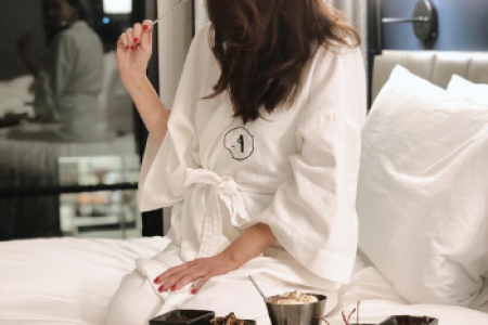 A woman wearing a Frette robe and sitting on a bed