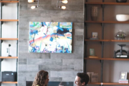 A man and a woman sitting in the library-lounge at Archer Hotel Florham Park