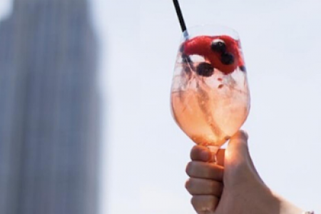 A hand holding a cocktail with the Empire State Building in the background