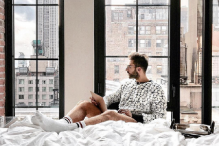 A man sitting in a hotel room and looking out the window