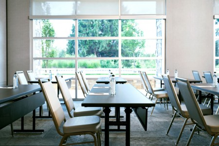 Classroom A — with tables, chairs and floor-to-ceiling natural light
