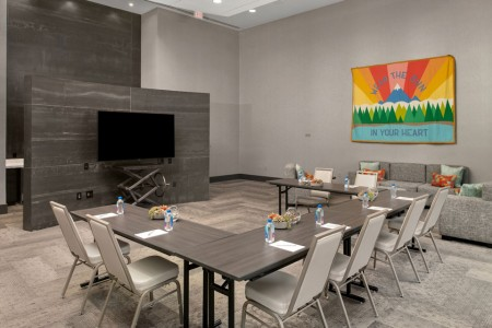 Hospitality Lounge — conference table, chairs, sofa and flat-screen TV