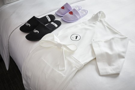 Whimsical slippers and Frette robe on bed