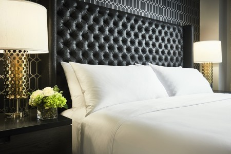 Archer King Suite - bedding detail with bedside lamps and large headboard