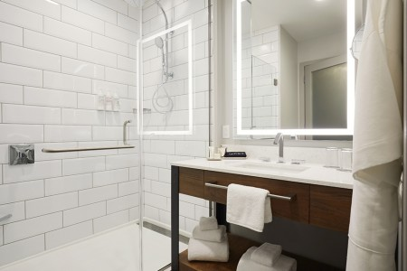 Modern bathroom with a subway-tiled walk-in shower and weathered iron vanity with lighted mirror