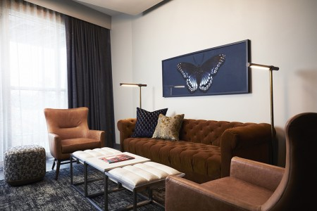 Archer's Den - living area featuring a dark caramel crushed velvet sofa and wingback chairs