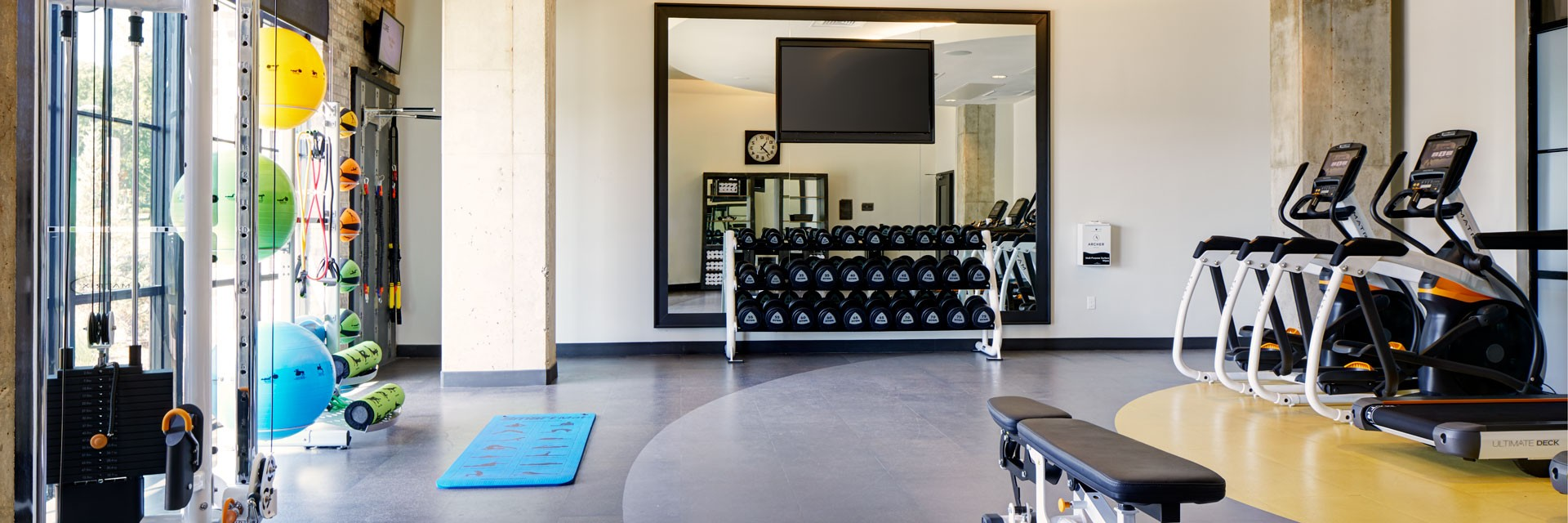 The fitness studio at Archer Hotel Florham Park, with free weights, treadmills and other exercise equipment